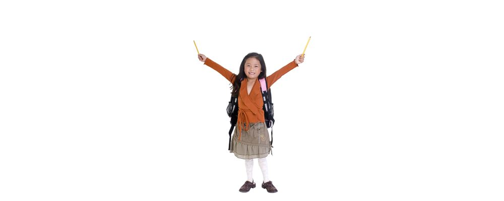 Little girl with a smile holding pencils in the air in both hands.